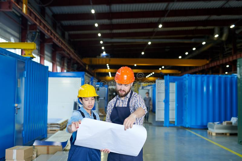 Engineers Studying Blueprints. Waist up portrait of two modern factory workers wearing hardhats holding blueprints while discussing production in workshop, copy royalty free stock photos