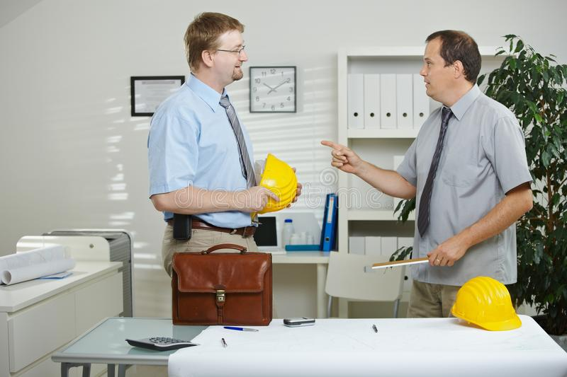 Engineers talking at office stock images