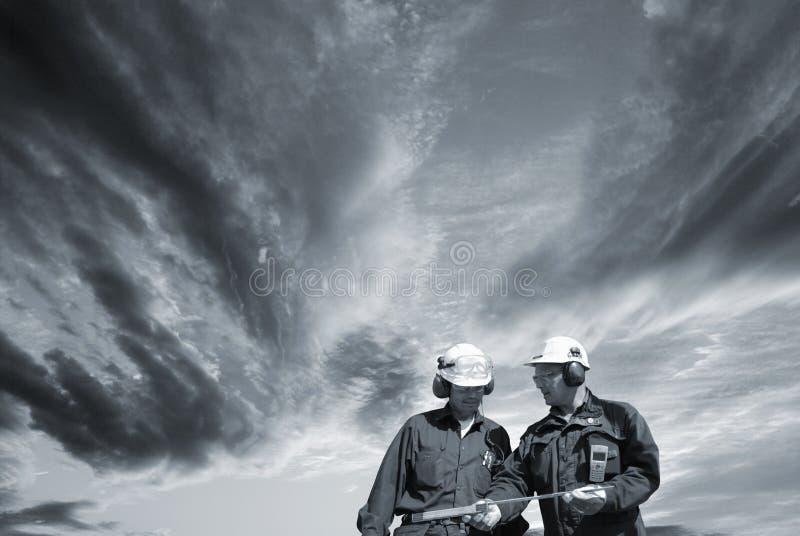 Engineers walking under dark clouds royalty free stock image