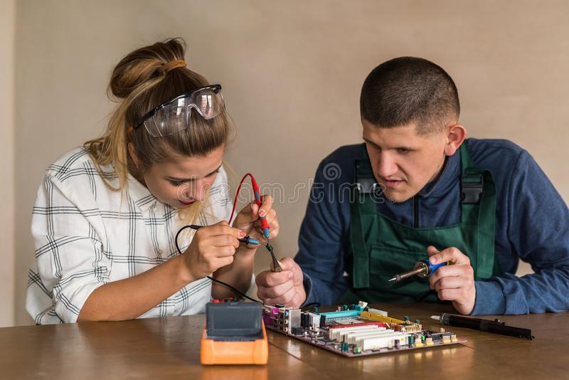 Engineers working with motherboard repairing some details stock photography
