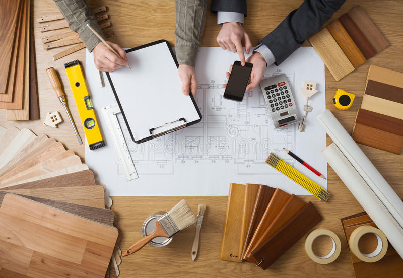 Engineers working together on a building project. Business people working together on a building project, desktop top view with tools, wood swatches, mobile royalty free stock images