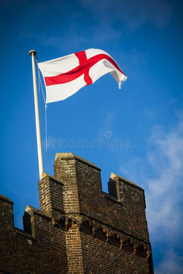 England flag flying over castle walls on sunny day stock images
