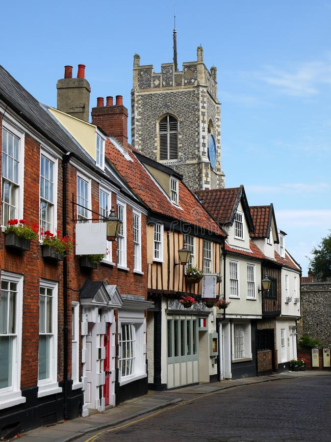 England: historic street in Norwich. Historic cottages and shops in Norwich, England, with flint stone parish church in background royalty free stock photos