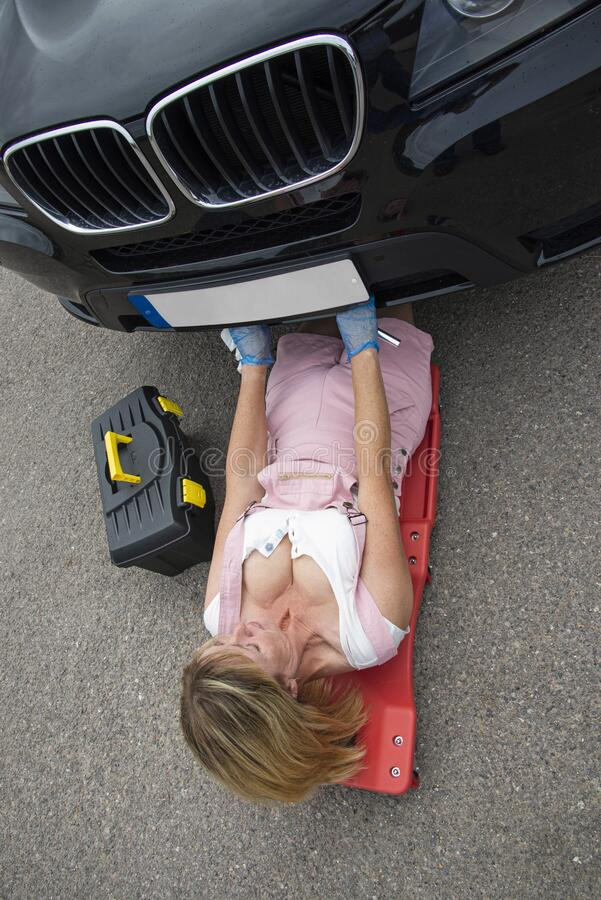 Female mechanic on a crawler to access underside of a automobile. stock photo