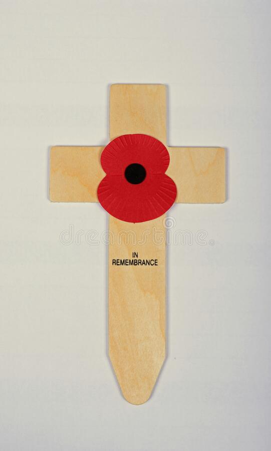 A single red poppy on a small wooden cross. royalty free stock photos