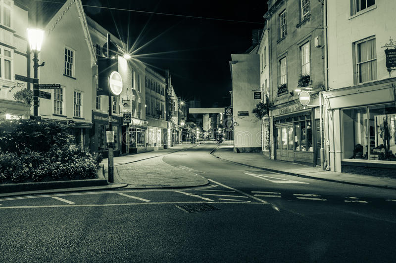 ENGLAND, WELLS - 20 SEP 2015: High Street by night, black and wh. Ite photography, split toning, night photography royalty free stock photo