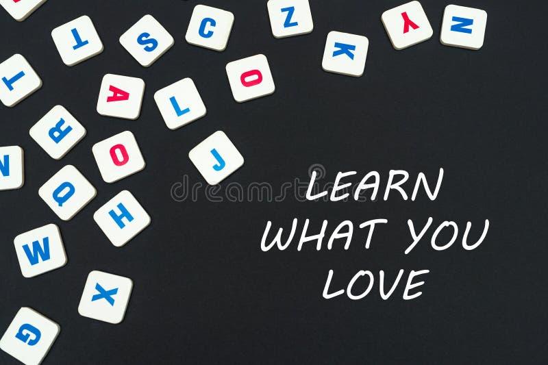 Englisch färbte quadratische Buchstaben zerstreut auf schwarzen Hintergrund mit Text lernt, was Sie lieben stockfotografie