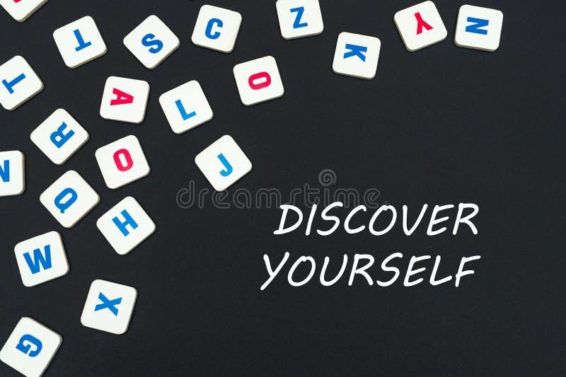 Englisch färbte quadratische Buchstaben zerstreut auf schwarzen Hintergrund mit Text sich entdeckt stockbilder