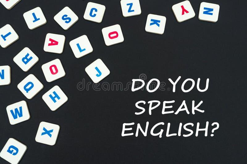 Englisch färbte quadratische Buchstaben zerstreut auf schwarzen Hintergrund mit Text Sie spricht Englisch lizenzfreie stockbilder