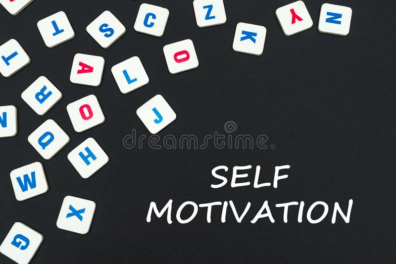 Englisch färbte quadratische Buchstaben zerstreut auf schwarzen Hintergrund mit Textselbstmotivation lizenzfreies stockfoto
