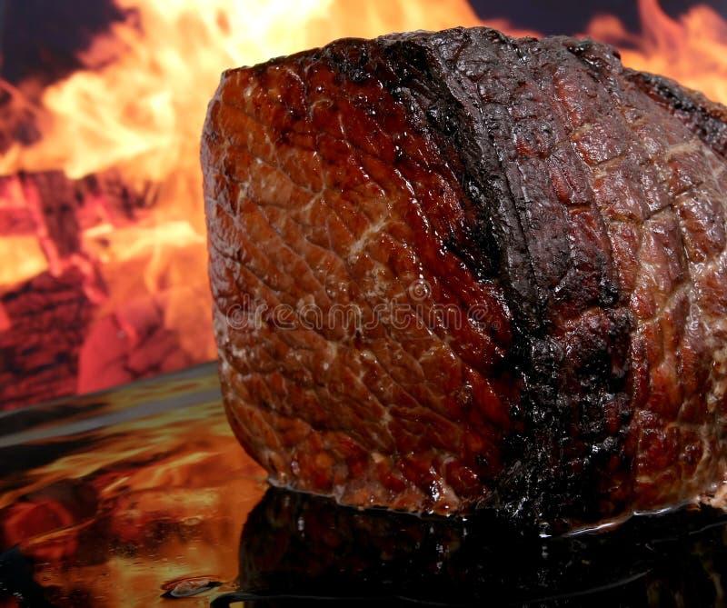 Englischbratenfleisch durch Feuer mit Flammen lizenzfreie stockfotografie