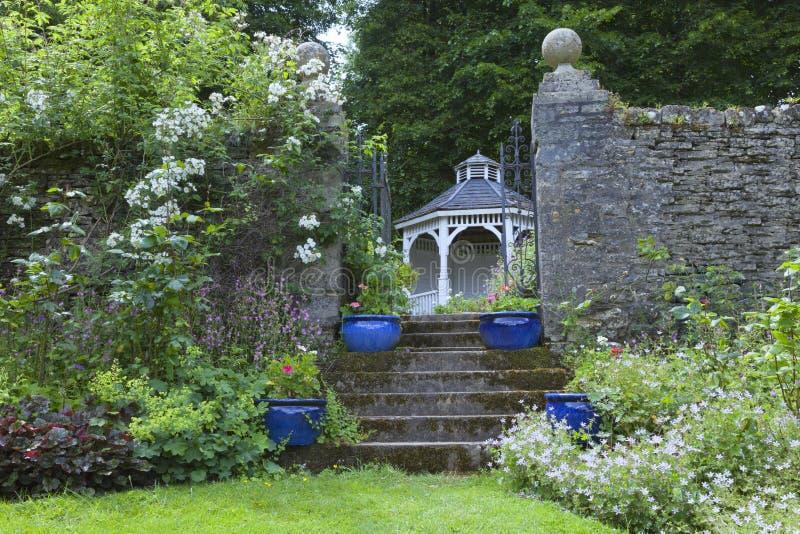 Englischer Garten mit blauen Töpfen, Rosen, alte hölzerne Laube lizenzfreie stockbilder
