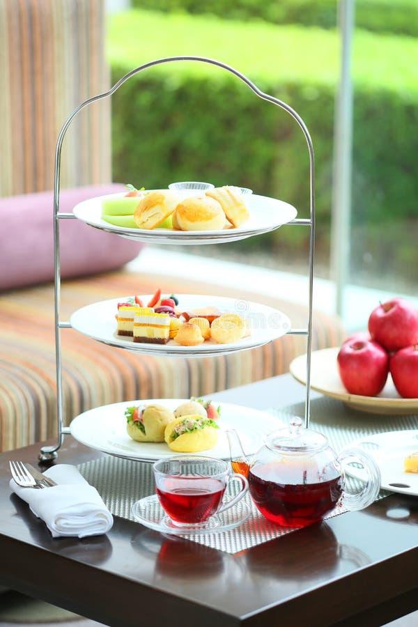 Englischer Kurs des hohen Tees mit kleinem Kuchen, Muffin, Apfel und Creme herein stockfotos