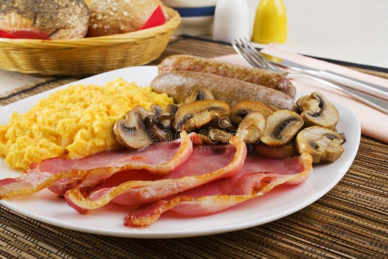 Englisches Frühstück mit durcheinandergemischten Eiern und Würsten lizenzfreie stockbilder