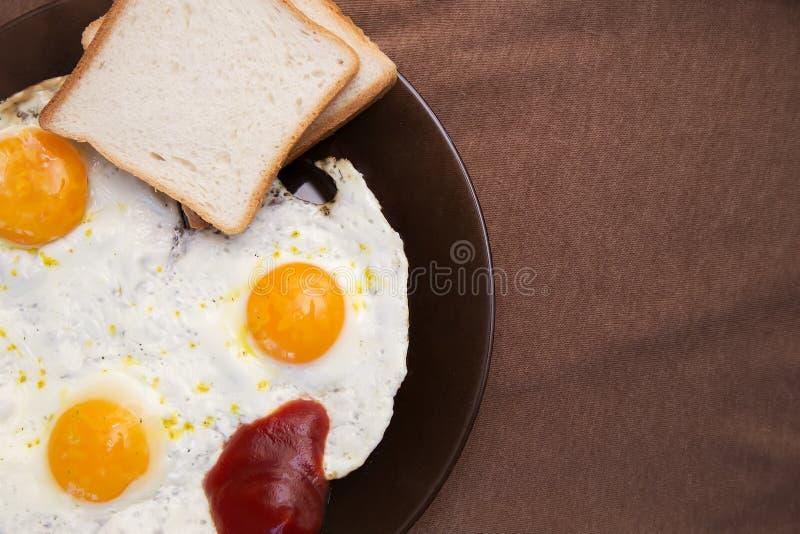 Englisches Frühstück, Spiegeleier mit Toast auf einer alten strukturierten Tabelle lizenzfreie stockfotografie