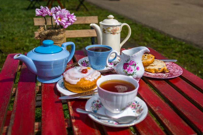 English afternoon Tea & Cake for two. English tea and cake picnic outside on a table for afternoon tea royalty free stock photo