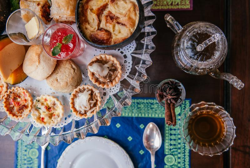 English afternoon tea with scone and puff pastries, tea cup and teapot top view. Traditional elegance English afternoon tea with scone, assorted tart and puff stock image