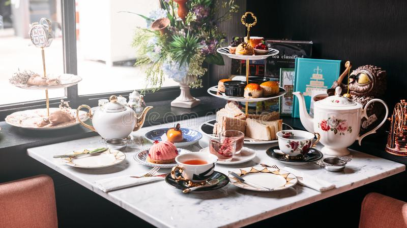 English afternoon tea set including hot tea, pastry, scones, sandwiches and mini pies on marble top table.  stock images