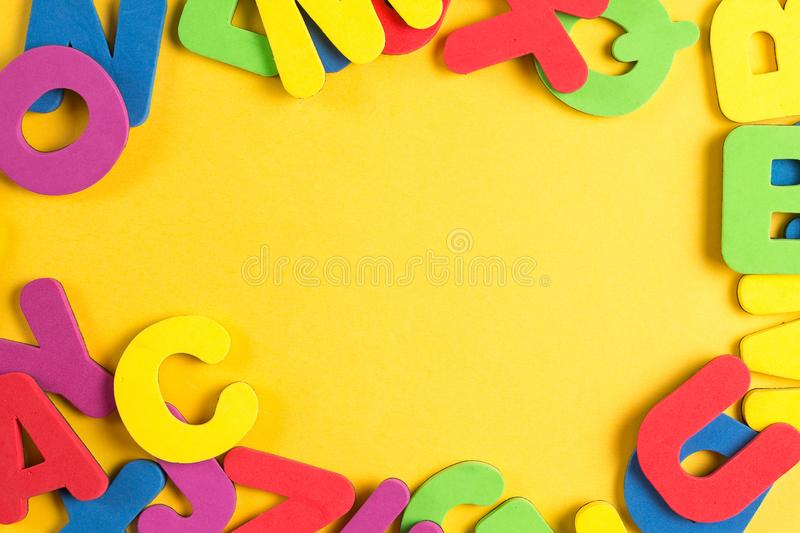 English Alphabet Random Circle Frame Flat Lay. Different Colorful Communication Word Game Yellow Background. Educational System School Concept Spell Letter royalty free stock photos