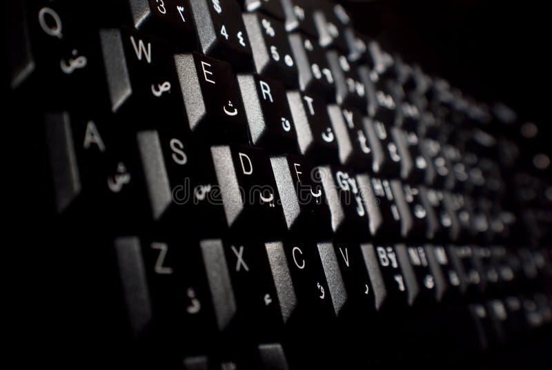 English / Arabic Computer Keyboard. Black computer keyboard with English and Arabic lettering stock images