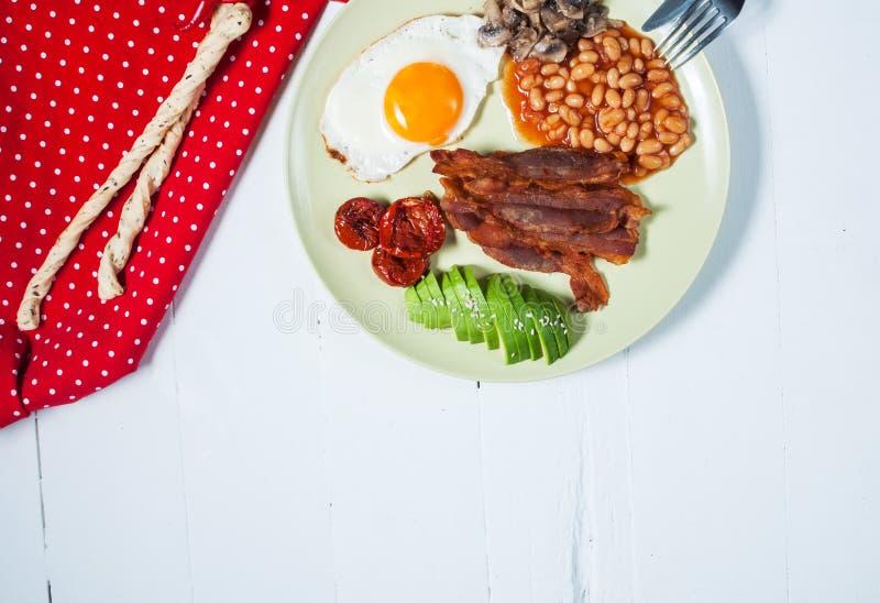 English breakfast of bacon, fried egg, beans, mushrooms, avocado royalty free stock photography