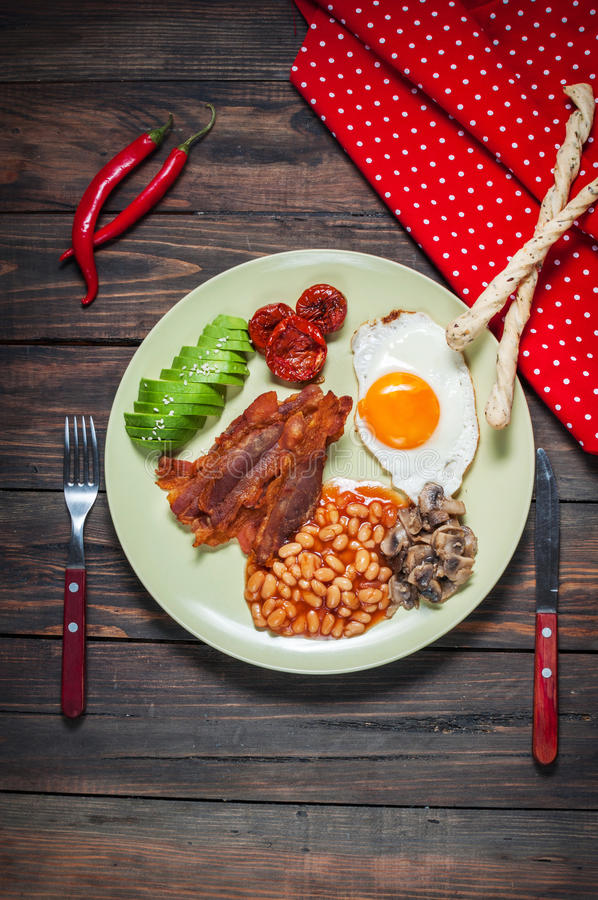 English breakfast of bacon, fried egg, beans, mushrooms, avocado royalty free stock photo