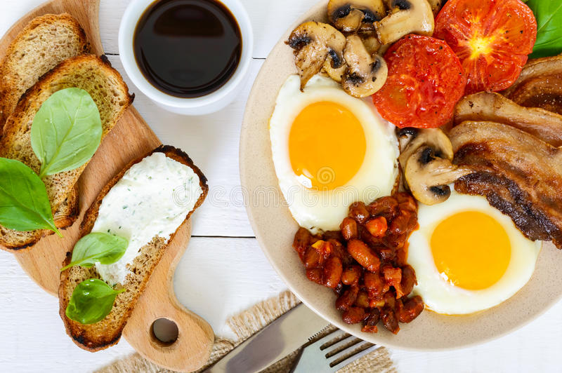 English breakfast: eggs, bacon, beans in tomato sauce, mushrooms, tomatoes, toast with cream cheese and a cup of coffee. On a white wooden background. A stock photos