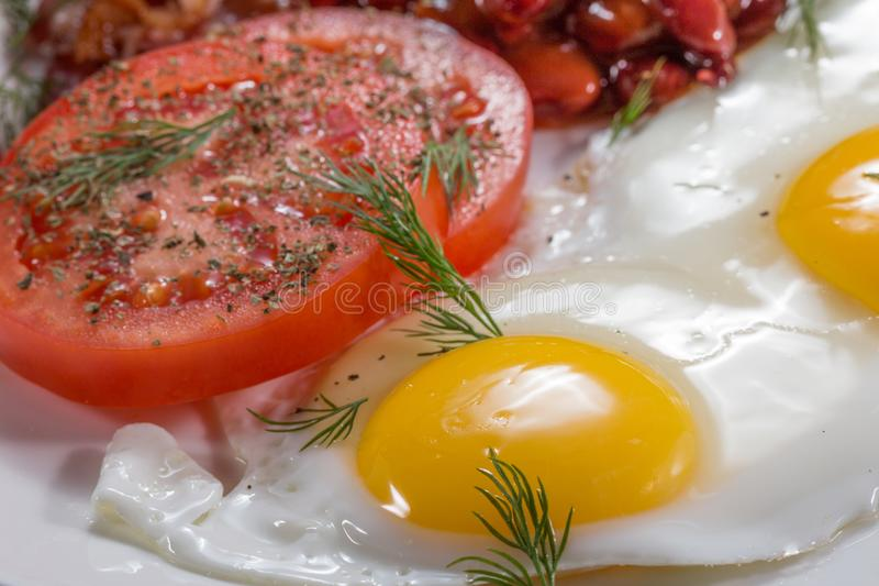 English breakfast with eggs, beans, bacon and sausages royalty free stock photo