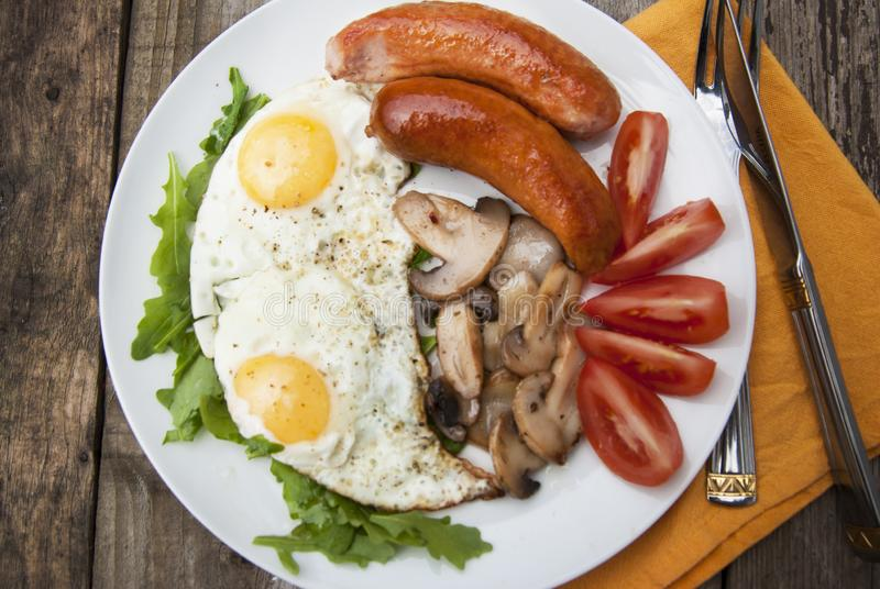 English breakfast. Eggs, sausages, mushrooms, tomatoes, toast bread. Eating tasy food over rustic wooden table. Food photography royalty free stock photography