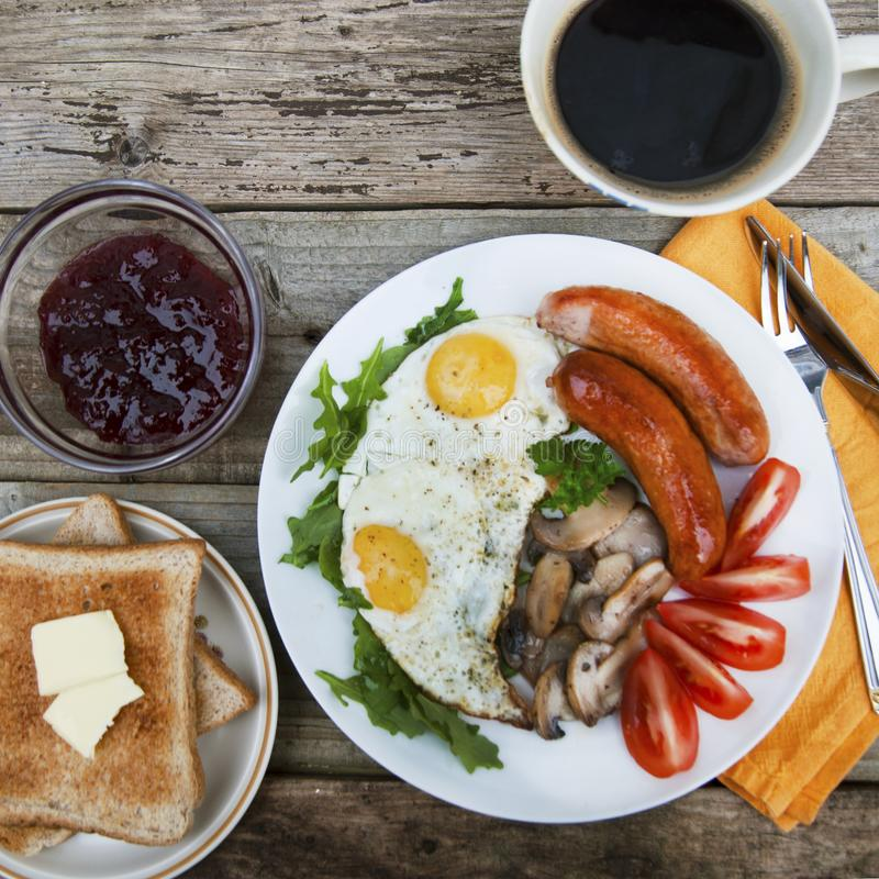 English breakfast. Eggs, sausages, mushrooms, tomatoes, toast bread. Eating tasy food over rustic wooden table. Copy space. Square. English breakfast. Eggs royalty free stock photo
