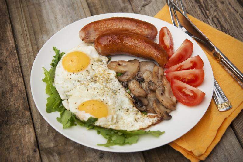 English breakfast. Eggs, sausages, mushrooms, tomatoes, toast bread. Eating tasy food over rustic wooden table. Copy space. English breakfast. Eggs, sausages stock photography