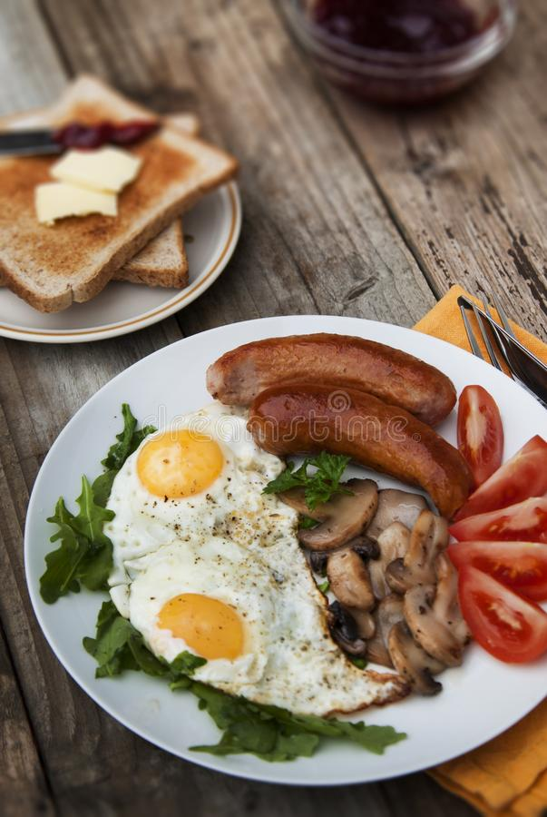 English breakfast. Eggs, sausages, mushrooms, tomatoes, toast bread. Eating tasy food over rustic wooden table. Food photography royalty free stock images