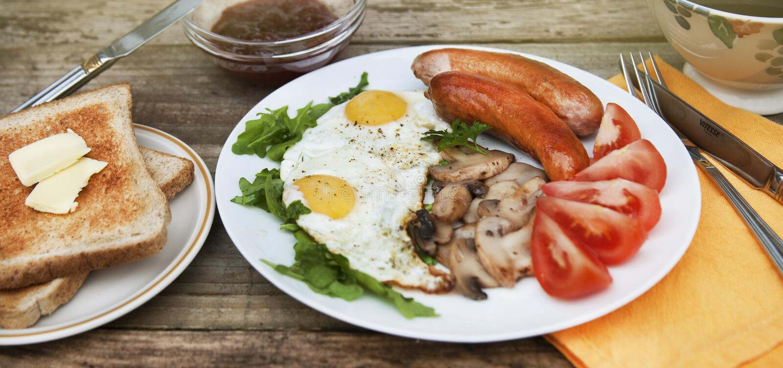 English breakfast. Eggs, sausages, mushrooms, tomatoes, toast bread. Eating tasy food over rustic wooden table. Copy space. Banner. English breakfast. Eggs stock photography