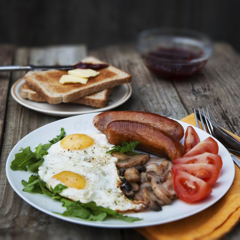 English breakfast. Eggs, sausages, mushrooms, tomatoes, toast bread. Eating tasy food over rustic wooden table. Copy space. Square. English breakfast. Eggs royalty free stock photos
