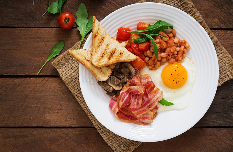 English breakfast - fried egg, beans, tomatoes, mushrooms, bacon and toast. Top view royalty free stock image