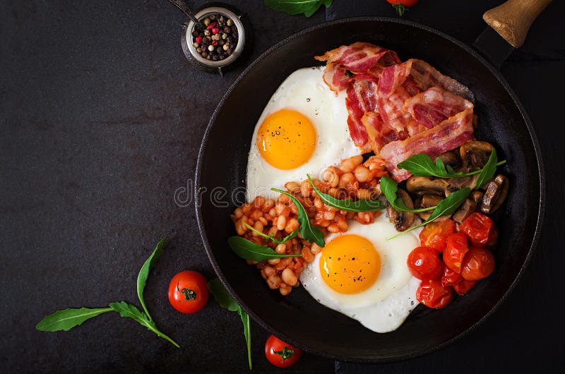 English breakfast - fried egg, beans, tomatoes, mushrooms, bacon and toast. Top view stock image