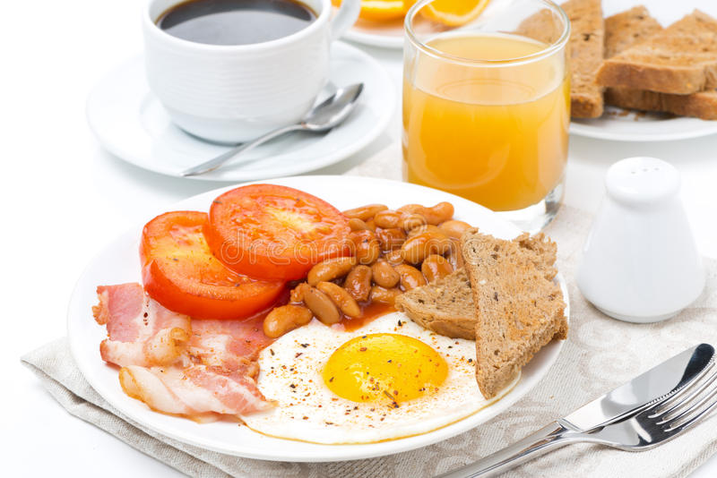 English breakfast with fried eggs, bacon, beans, coffee, juice. English breakfast with fried eggs, bacon, beans, coffee and juice, isolated stock image