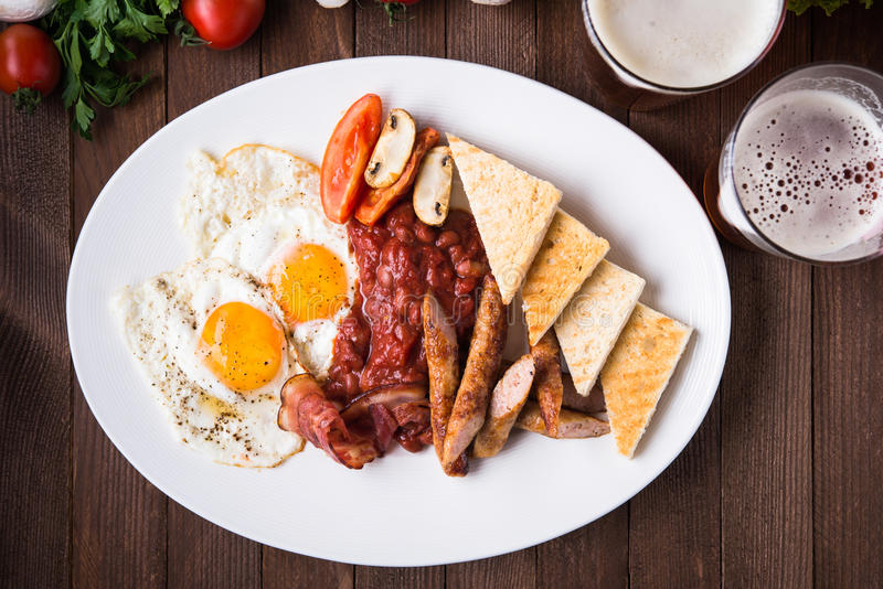 English breakfast (fried eggs, beans, roasted bacon, sausages and vegetables) on dark wood background. Top view royalty free stock images