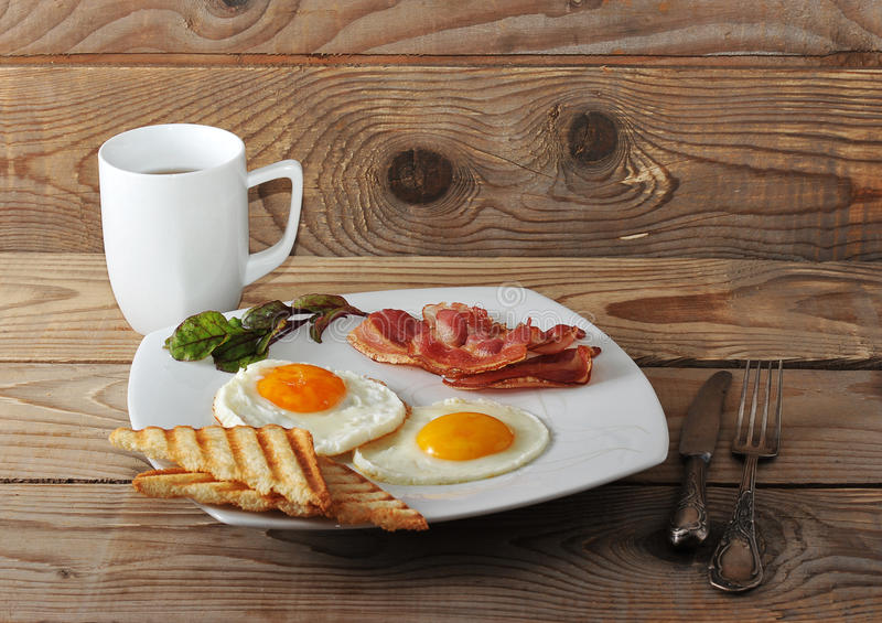 English Breakfast - scrambled eggs, bacon, fried toast and tea. On a wooden rustic background royalty free stock photos