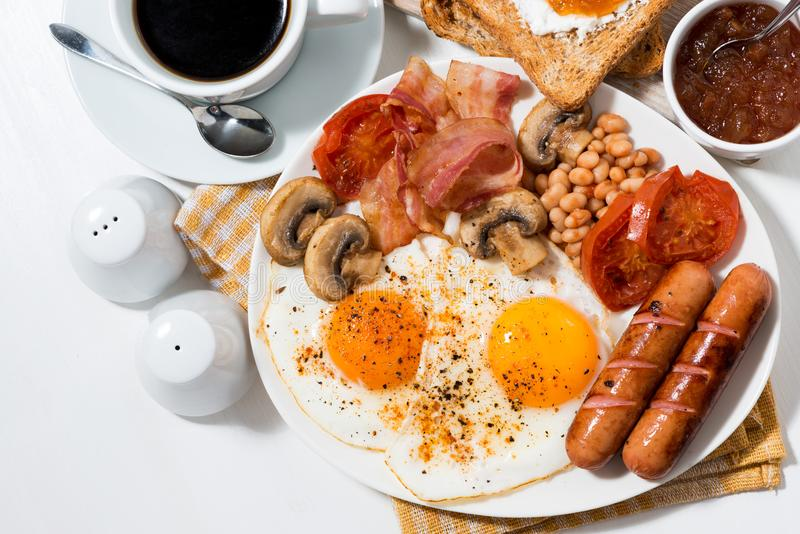 English breakfast of scrambled eggs with bacon and sausages stock photo
