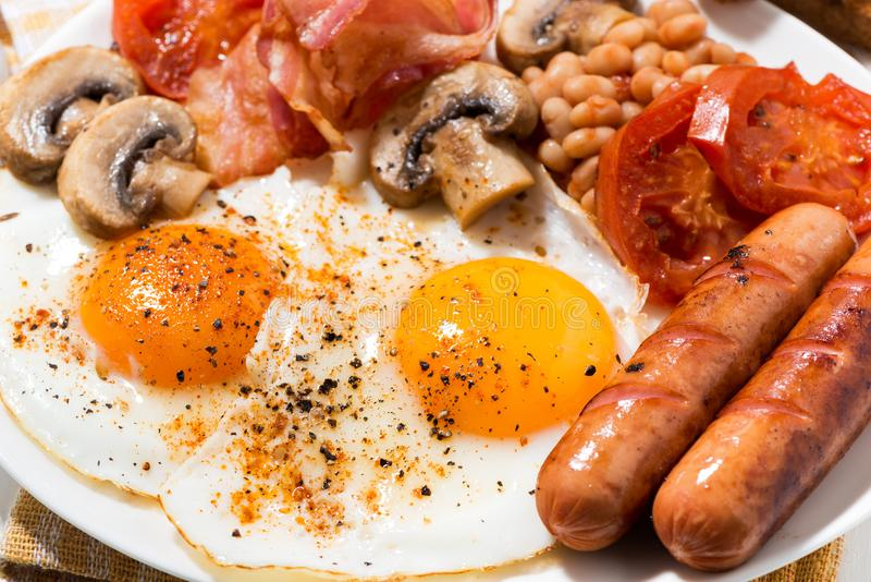 English breakfast of scrambled eggs with bacon, sausages royalty free stock photos