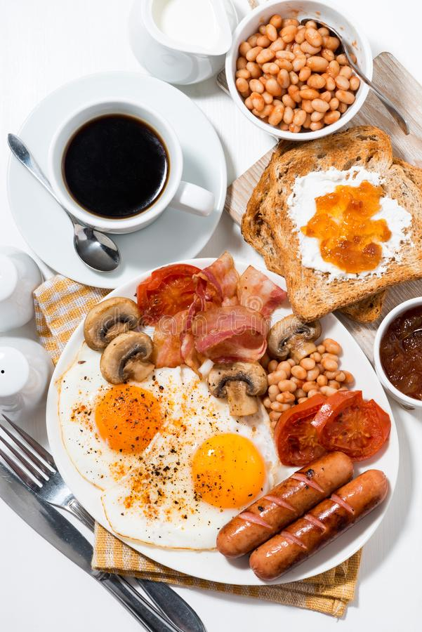 English breakfast of scrambled eggs with bacon, sausages and vegetables on white table, vertical top view stock images