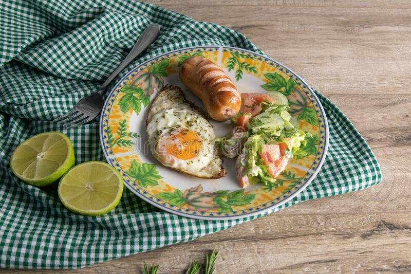 English breakfast, scrambled eggs with sausage and cabbage salad, next to it is a lime cut in half, a plate stands on a wooden. Table royalty free stock photography