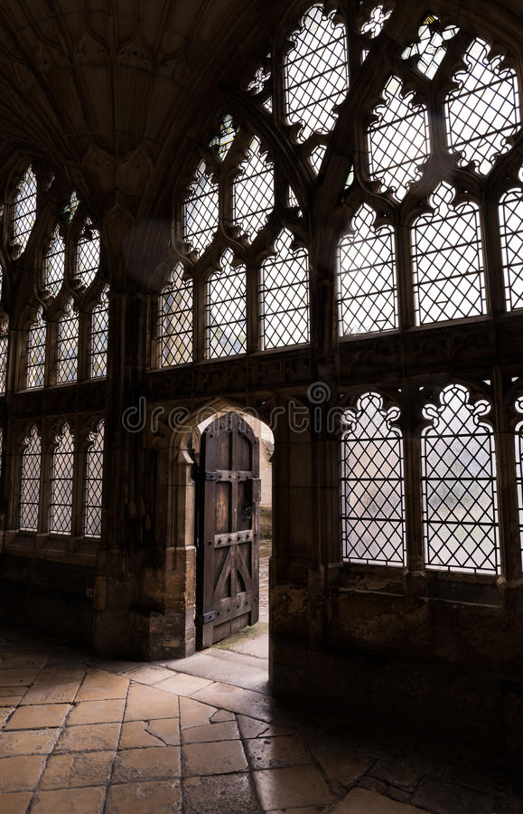 English Cathedral Stone floor, walls, glass and light coming through old wooden door royalty free stock photo
