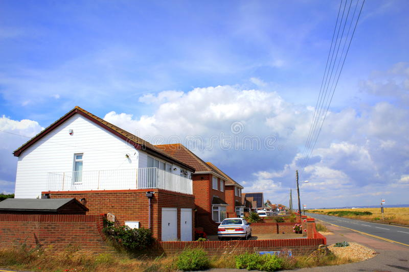 English Channel coastal road United Kingdom. Dungeness coastal road and roadside houses of Lydd-on-Sea village.Lydd-on-Sea is a modern village, mostly built stock photography