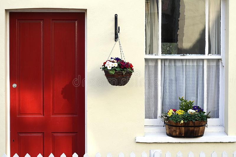 English Cottage. Traditional English cottage with spring flowers in baskets royalty free stock photo