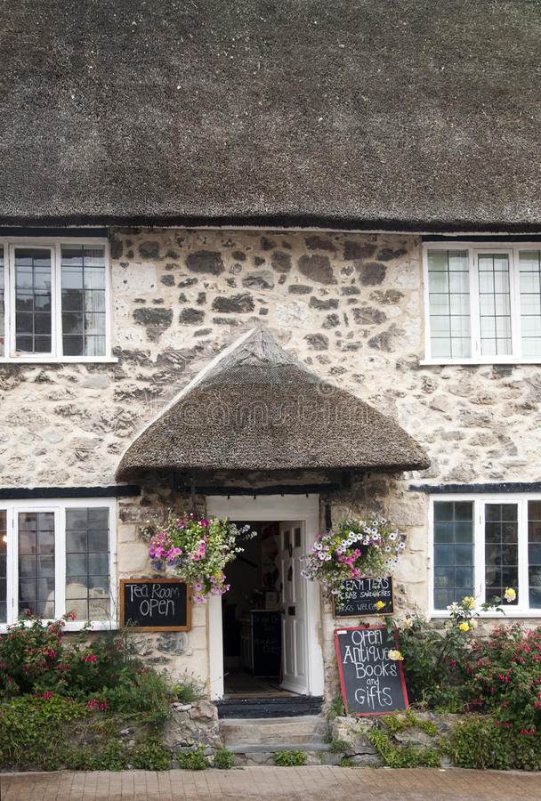 English cottage. Entrance to English tea room in a thatched cottage with hanging flower baskets and flowers; Devon, England, UK stock photos