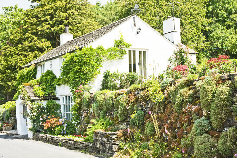English cottage with attractive garden. An image of an ideal English country cottage with a road side rockery and flower garden stock images
