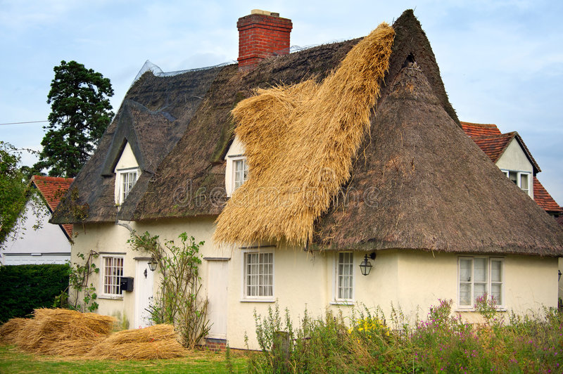 English Cottage being thatched. With new thatch. All ID removed stock photography