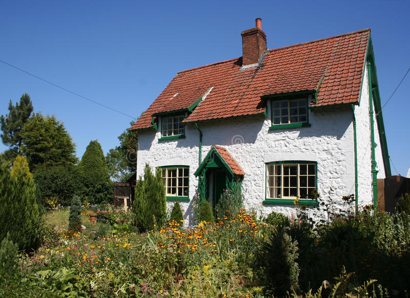 English cottage. Closeup of typical English white wall cottage and garden royalty free stock photography